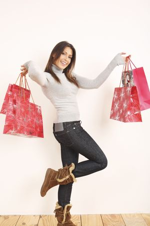 クリスマスの買い物袋を保持している女性 写真素材
