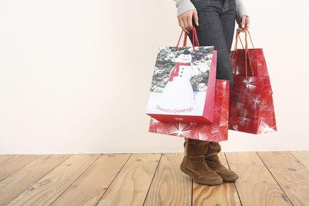 Mujer que sostiene bolsos de compras de Navidad