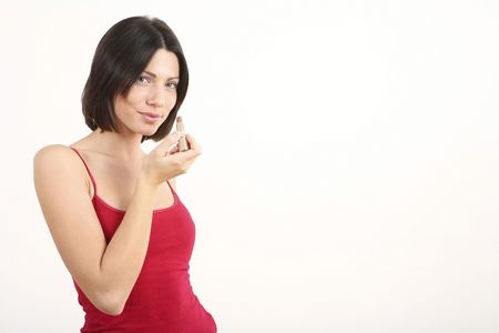 puckering lips: Woman puckering her lips while holding lipstick
