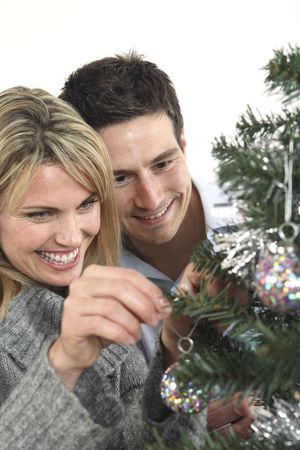 christmas decorations with white background: Man and woman decorating christmas tree