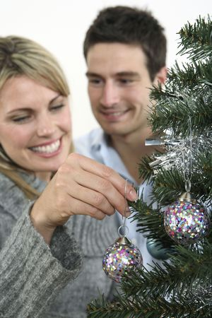 Woman hanging christmas bauble, man watching Stock Photo - 2966219