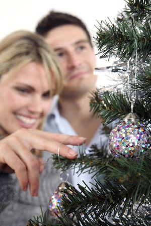 Woman hanging christmas bauble, man looking away photo