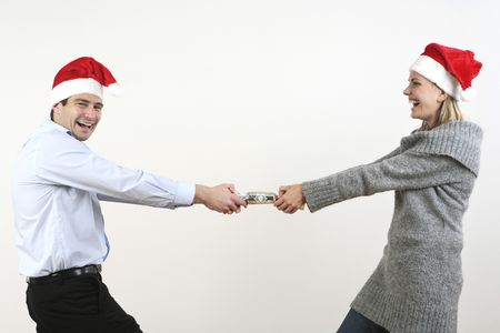 Man and woman pulling christmas cracker Stock Photo - 2966224