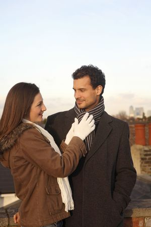 Woman adjusting man's scarf at the rooftop Stock Photo - 2966228