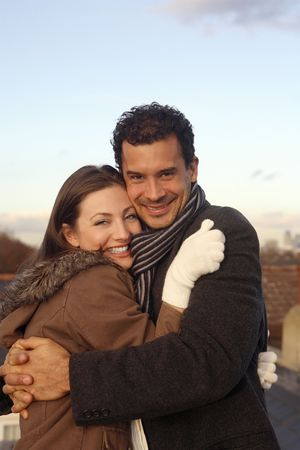 couple winter: Man and woman in winter clothing hugging at the rooftop