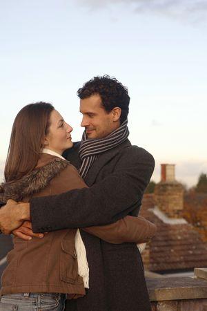 Hombre y mujer en la ropa del invierno que abraza en el tejado