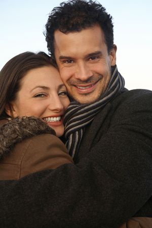 healthy llifestyle: Man and woman in winter clothing hugging at the rooftop
