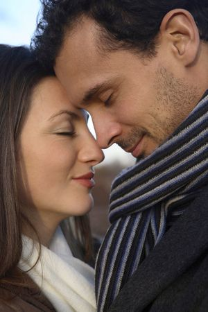 couple winter: Man and woman embracing, closing eyes