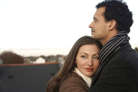 healthy llifestyle: Man and woman in winter clothing hugging, at the rooftop
