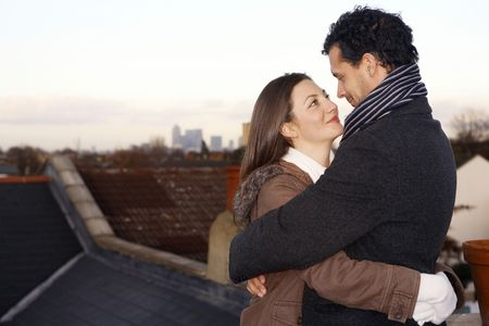 Man and woman in winter clothing hugging at the rooftop Stock Photo - 2966237