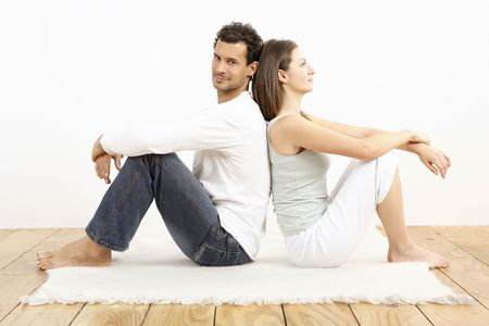 he: Man and woman sitting down, leaning back to back LANG_EVOIMAGES