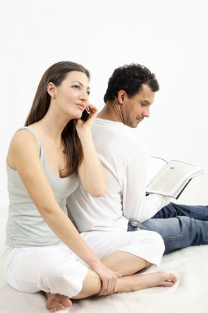 Woman talking on the mobile phone while man is reading a book Stock Photo - 2966262