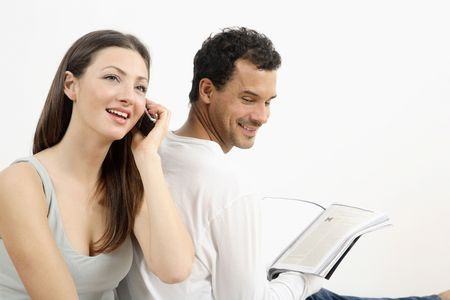 healthy llifestyle: Woman talking on the mobile phone while man is reading a book
