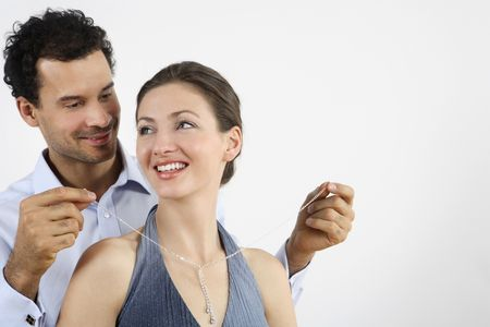 healthy llifestyle: Man putting on a necklace for his girlfriend LANG_EVOIMAGES