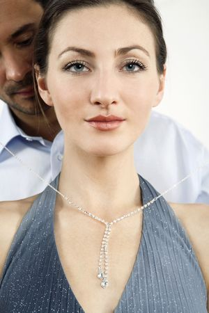Man putting on a necklace for his girlfriend Stock Photo - 2966274