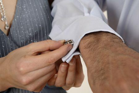 cufflink: Woman putting on a cufflink on mans shirt