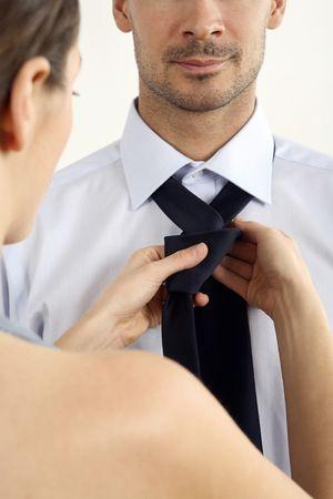 healthy llifestyle: Woman tying necktie for her boyfriend LANG_EVOIMAGES