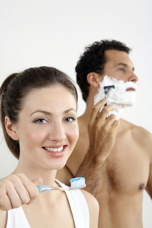 Woman about to brush her teeth with man shaving in the background photo
