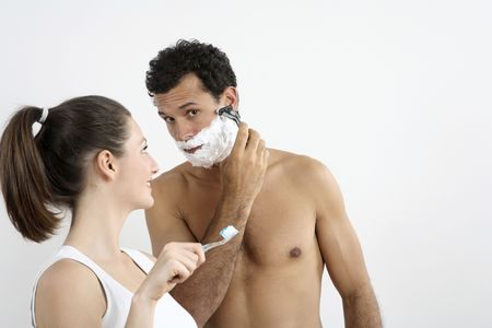 Woman about to brush her teeth with man shaving photo