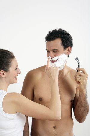Woman disturbing man shaving photo