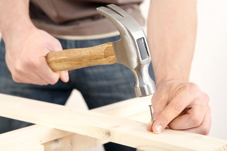 hammers: Man hammering nail into wood LANG_EVOIMAGES