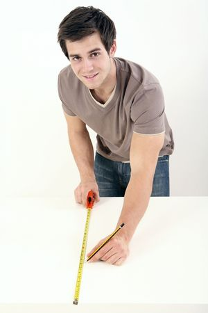 Man using tape measure on wooden board Stock Photo - 2966320