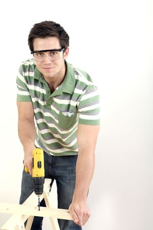 Man with safety goggles drilling wood Stock Photo - 2966328