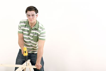 Man with safety goggles drilling wood Stock Photo - 2966329