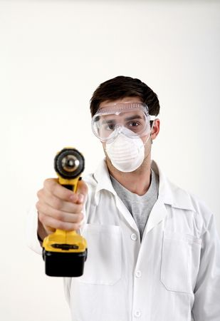 power drill: Man with safety mask and goggles pointing a power drill at the camera