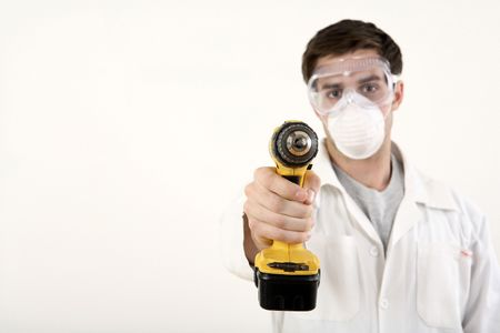 Man with safety mask and goggles pointing a power drill at the camera photo