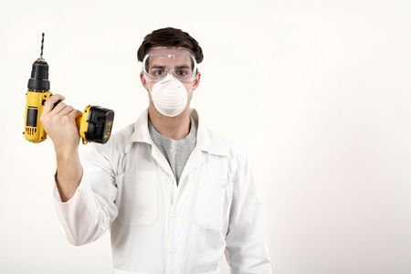 Man with safety mask and goggles holding a power drill photo