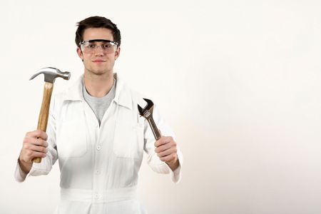 Man with safety goggles holding a hammer and adjustable spanner in each hand photo