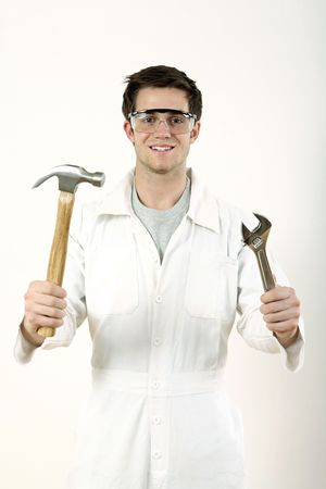 Man with safety goggles holding a hammer and a spanner in each hand photo