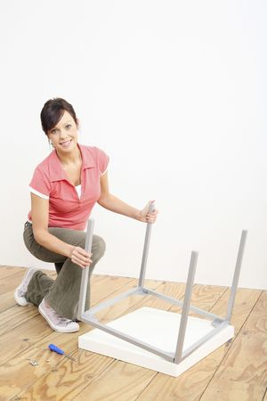 Woman assembling a table Stock Photo - 2966381