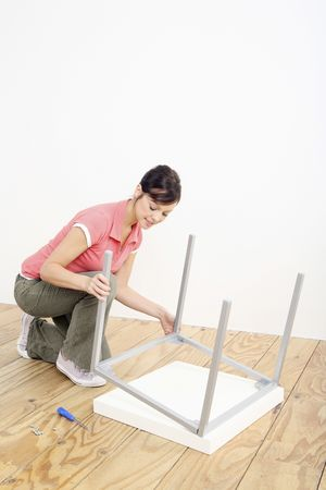 Woman assembling a table Stock Photo - 2966382