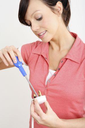 electric plug: Woman fixing an electric plug LANG_EVOIMAGES