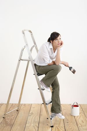 Woman with paintbrush looking up while sitting on ladder Stock Photo - 2966399