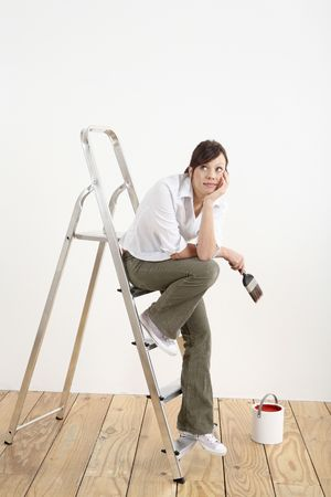 Woman with paintbrush looking away while sitting on ladder Stock Photo - 2966400