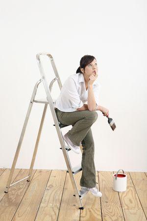 Mujer con pincel pensar mientras está sentado en escalera  Foto de archivo - 2966401