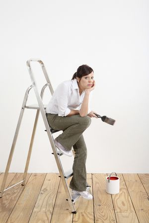 Woman with paintbrush sitting on ladder Stock Photo - 2966402