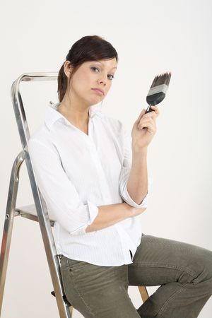 Woman with paintbrush sitting on ladder Stock Photo - 2966403