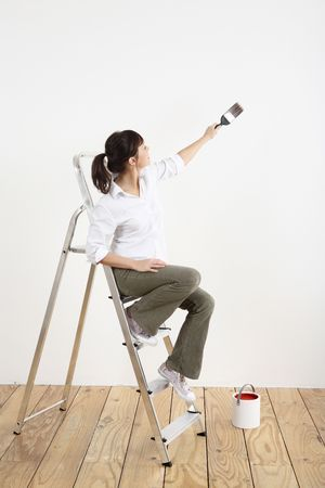 Woman sitting on ladder painting the wall Stock Photo - 2966404
