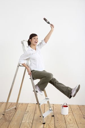 Woman with paintbrush sitting on ladder Stock Photo - 2966405
