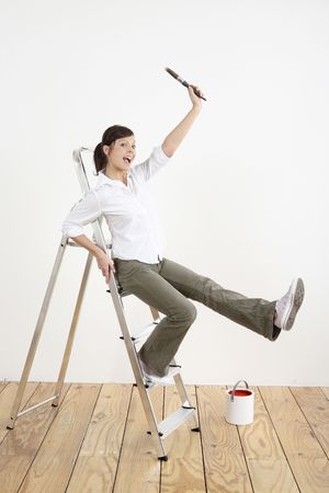 Woman with paintbrush sitting on ladder Stock Photo - 2966406