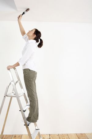 painting: Woman standing on ladder painting the ceiling