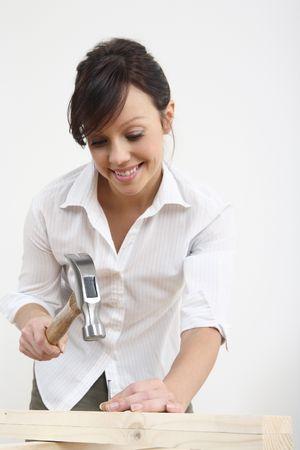Woman hammering nail into wood Stock Photo - 2966408