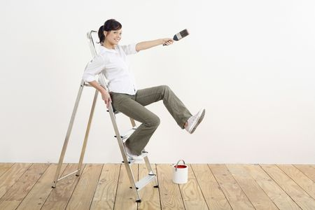 Woman with paintbrush sitting on ladder Stock Photo - 2966409