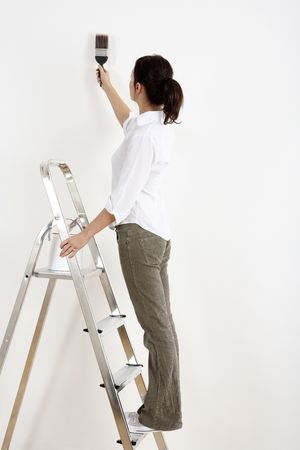 Woman standing on ladder painting the wall