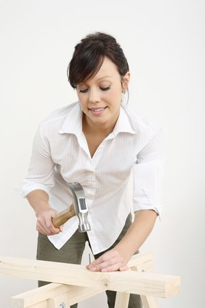Woman hammering nail into wood Stock Photo - 2966411