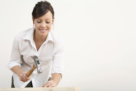 hammering: Woman hammering nail into wood